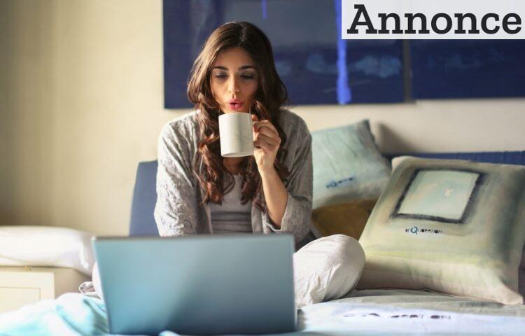 Ung kvinde ved computer med te